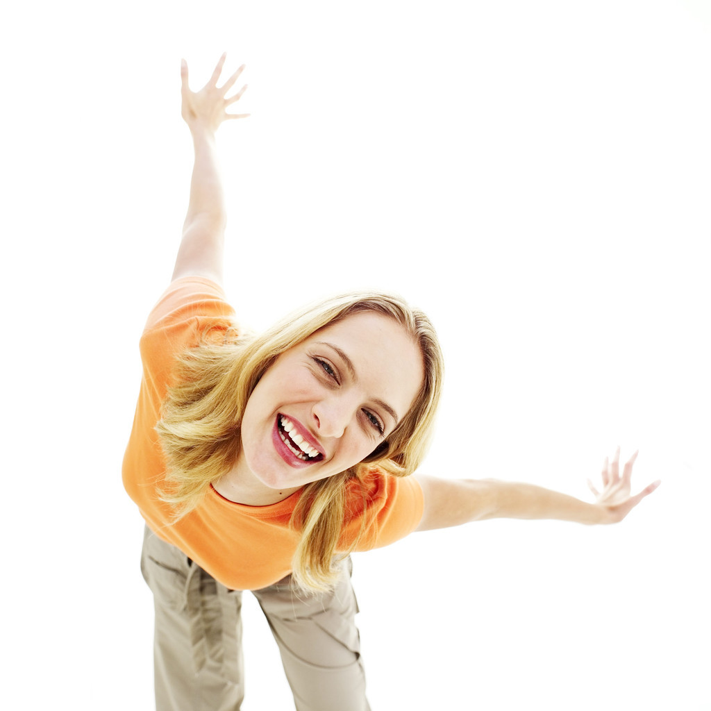 Young Woman Bending Down and Smiling with Arms Stretched Back
